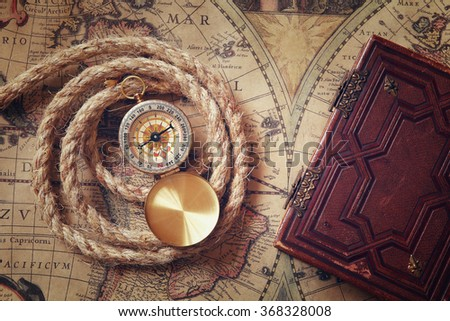 image of old compass and rope next to old book on vintage map  - stock photo