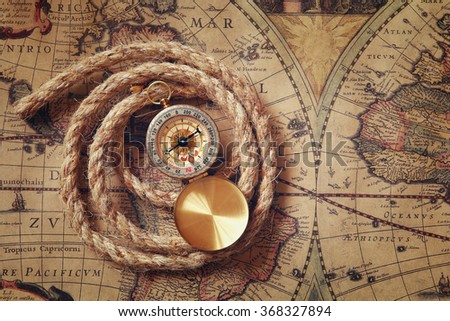 image of old compass and rope on vintage map  - stock photo