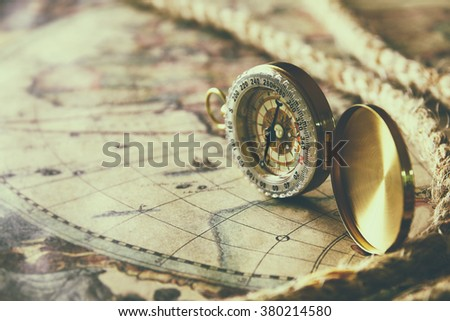 image of old compass and rope on vintage map. vintage filtered and toned - stock photo