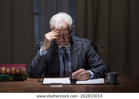 Image of old lonely businessman working at night - stock photo