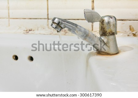 image of old sink with damaged water tap . - stock photo