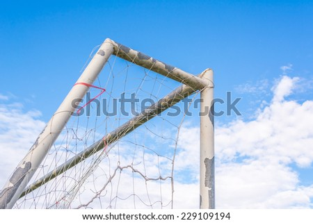 image of old soccer goal with blue sky - stock photo