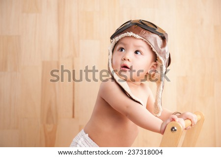 Image of one year old East Asian baby boy standing on wooden background, sweet little baby dreaming of being pilot - stock photo