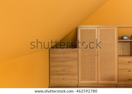 Image of orange attic room with simple wooden furniture