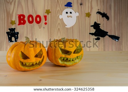 image of orange Halloween pumpkin on wooden table with wood background.