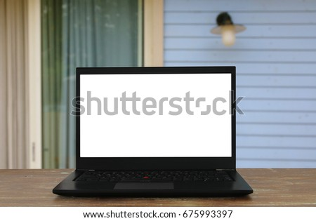 Image of outdoor with open laptop and empty white screen for copy space.