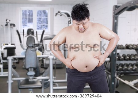 Image of overweight man standing in the fitness center while holding and looking his stomach - stock photo