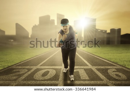 Image of overweight person running on the field with numbers 2016, shot in the morning