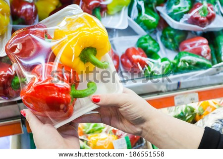 Image of packaged bell pepper with woman hand in the supermarket - stock photo