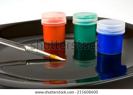 image of paints and brush on a black plate - stock photo