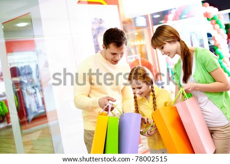 Image of parents showing their daughter what they bought in the mall
