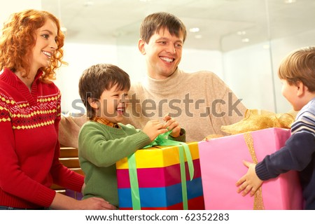 Image of parents with son looking at boy with big pink gift box