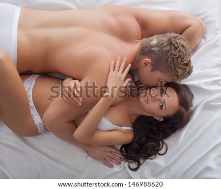 Image of passionate lovers hugging in bed - stock photo