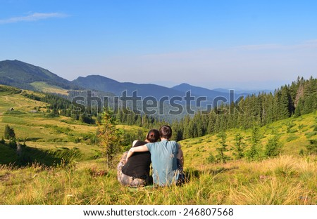 Image of people who are sitting on grass while looking far on the landscape - stock photo