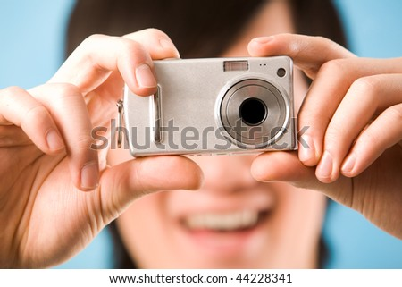 Image of photo camera in male hands ready to make a shot