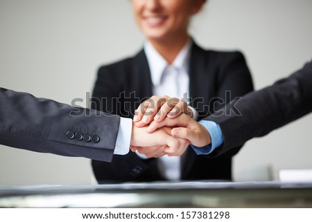 Image of pile of hands of business partners on background of businesswoman - stock photo