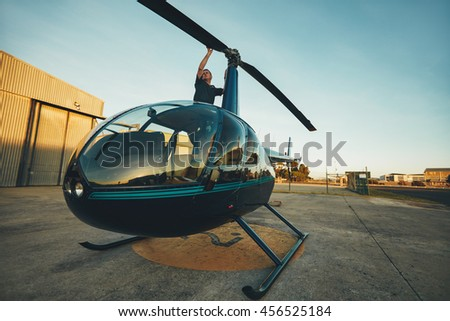 Image of pilot checking the helicopter rotor blades at the airfield. Man inspecting his aircraft before a flight. - stock photo