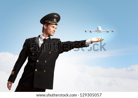 Image of pilot touching sky against airplane background