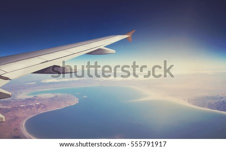 Image of plane and wing with blue sea, mountains, and coastline. Horizont line and sunrise.
