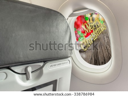 image of plane window and Christmas ornaments on wood background.