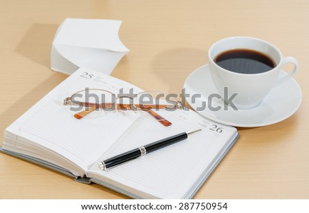 Image of planner , coffee cup pen and glasses - stock photo