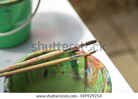 Image of plastic water bucket with paint and drawing brushes for art design background  - stock photo