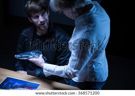 Image of police officer showing gun from crime scene - stock photo