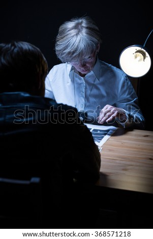 Image of policewoman analysing evidence in front of suspect - stock photo