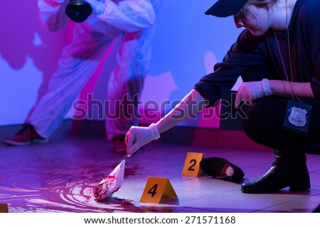 Image of policewoman working on a murder scene - stock photo