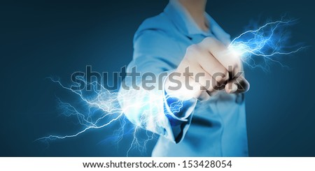 Image of powerful businesswoman holding lightning in fist - stock photo