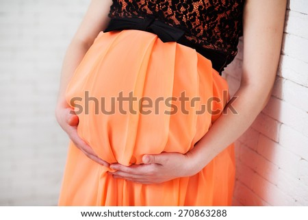 Image of pregnant woman touching her belly with hands. Pregnant woman caressing her belly. - stock photo