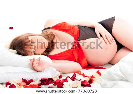 Image of pregnant woman touching her belly with hands. Resting on her bed