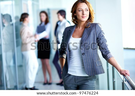 Image of pretty business leader with interacting partners at background - stock photo