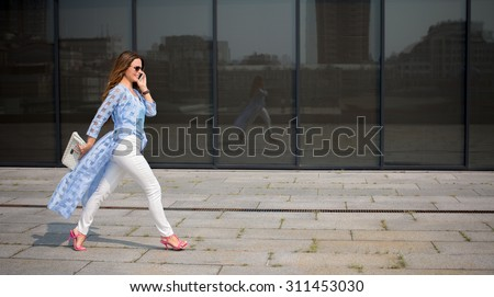 Image of pretty businesswoman holding little white bag and calling on the phone near office building. Long-haired woman is in a hurry.