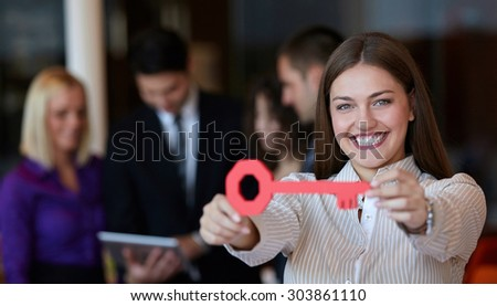 Image of pretty businesswoman looking at camera with key - stock photo