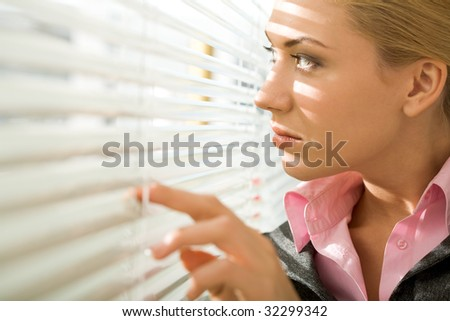 Image of pretty businesswoman looking through venetian blind in office - stock photo
