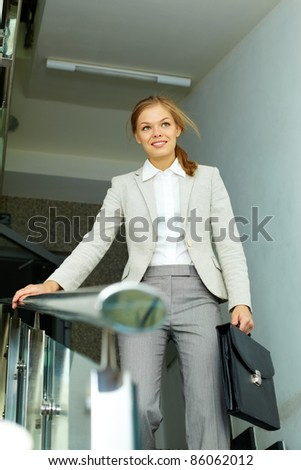 Image of pretty businesswoman with briefcase in the corridor of office building - stock photo