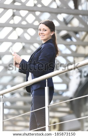 Image of pretty businesswoman with smart phone looking at camera