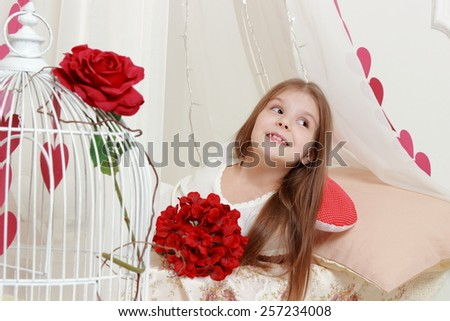 Image of pretty cheerful young girl with long hair holding a bouquet of red flowers in a romantic setting for Valentine's Day - stock photo