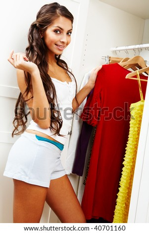 Image of pretty female looking at camera with wardrobe near by