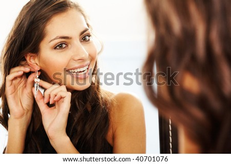 Image of pretty female looking in mirror and putting on earrings - stock photo
