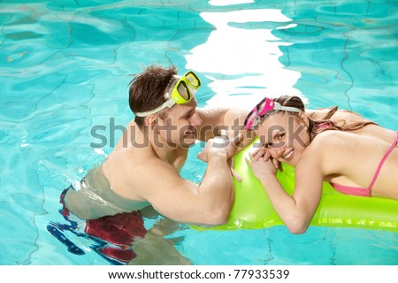 Image of pretty girl looking at camera in swimming pool with her boyfriend near by - stock photo