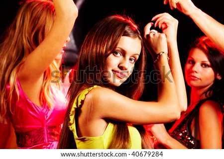 Image of pretty girl looking at camera while dancing on background of her friends