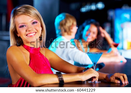 Image of pretty girl looking at camera with her friends behind in the nightclub