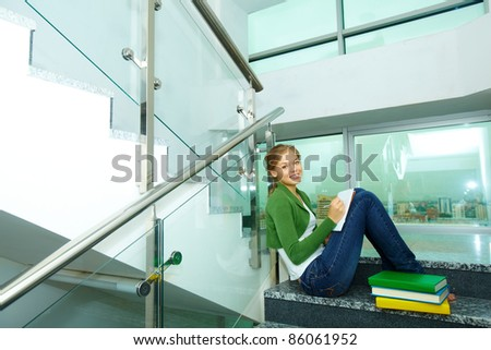 Image of pretty girl with books looking at camera on steps of college - stock photo