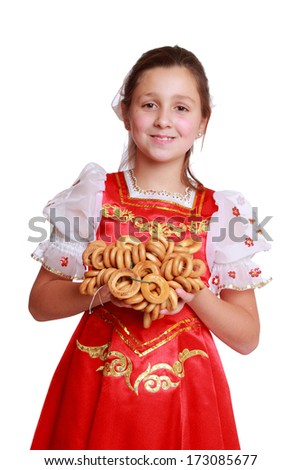 Image of pretty little girl with round cracknel isolated over white background on Holiday theme/Nice young girl with lovely smile wearing traditional russian costume
