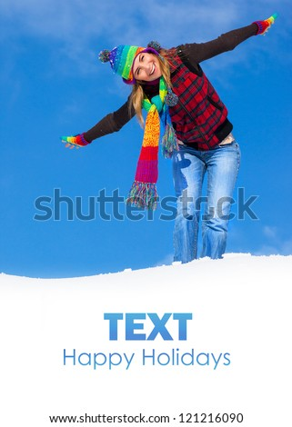 Image of pretty playful female having fun in winter park, cute woman standing with raised up hands on the top of snowy mountain, colorful hat and scarf, wintertime holidays, freedom concept - stock photo