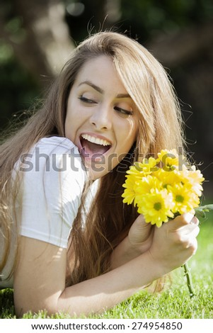 Image of pretty woman holding a beautiful yellow flowers. Cheerful girl resting, relaxation outdoor in springtime, vacation concept - stock photo