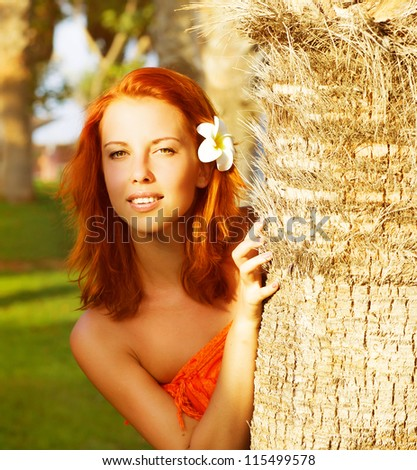 Image of pretty woman look out from behind a palm tree, closeup portrait of cute girl with frangipani flower in red hair, beautiful tropical nature, luxury spa resort, holiday and vacation concept - stock photo