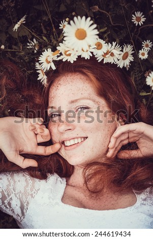 Image of pretty woman lying down on chamomile field, happy female holding in hand beautiful white flower, cheerful girl resting on daisy meadow, relaxation outdoor in springtime, vacation concept - stock photo